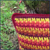 stripey crochet cushion against a tree