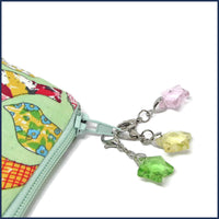 three glass star stitch markers on a project bag zip