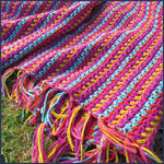 stripey crochet blanket on a lawn