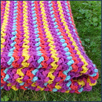 stripey crochet blanket folded on a lawn