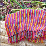 stripey crochet blanket on a veg patch with onions