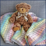rainbow crochet baby blanket close up with teddy