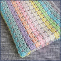 rainbow crochet baby blanket folded on a chair