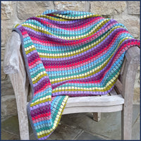 rainbow crochet blanket on a wooden chair