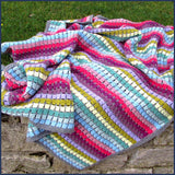 rainbow crochet blanket on a garden wall