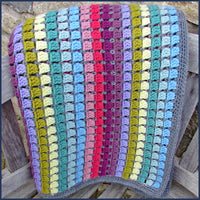 rainbow crochet blanket folded on a chair