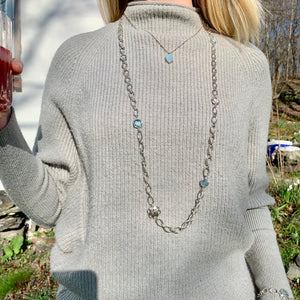 Cascade Sky Blue Topaz Infinity Necklace shown wearing sweater with Sabine pendant Hannah Daye & Co