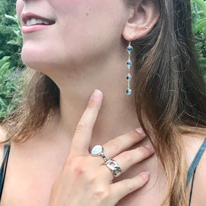 wearing Cascade Blue Topaz 4 stone earring with Bordillo and Sabine NS Rings Hannah Daye & Co