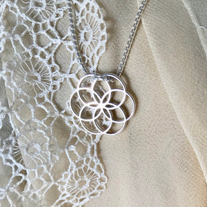 Rosette Plat Charm necklace on lace cloth Hannah Daye & Co