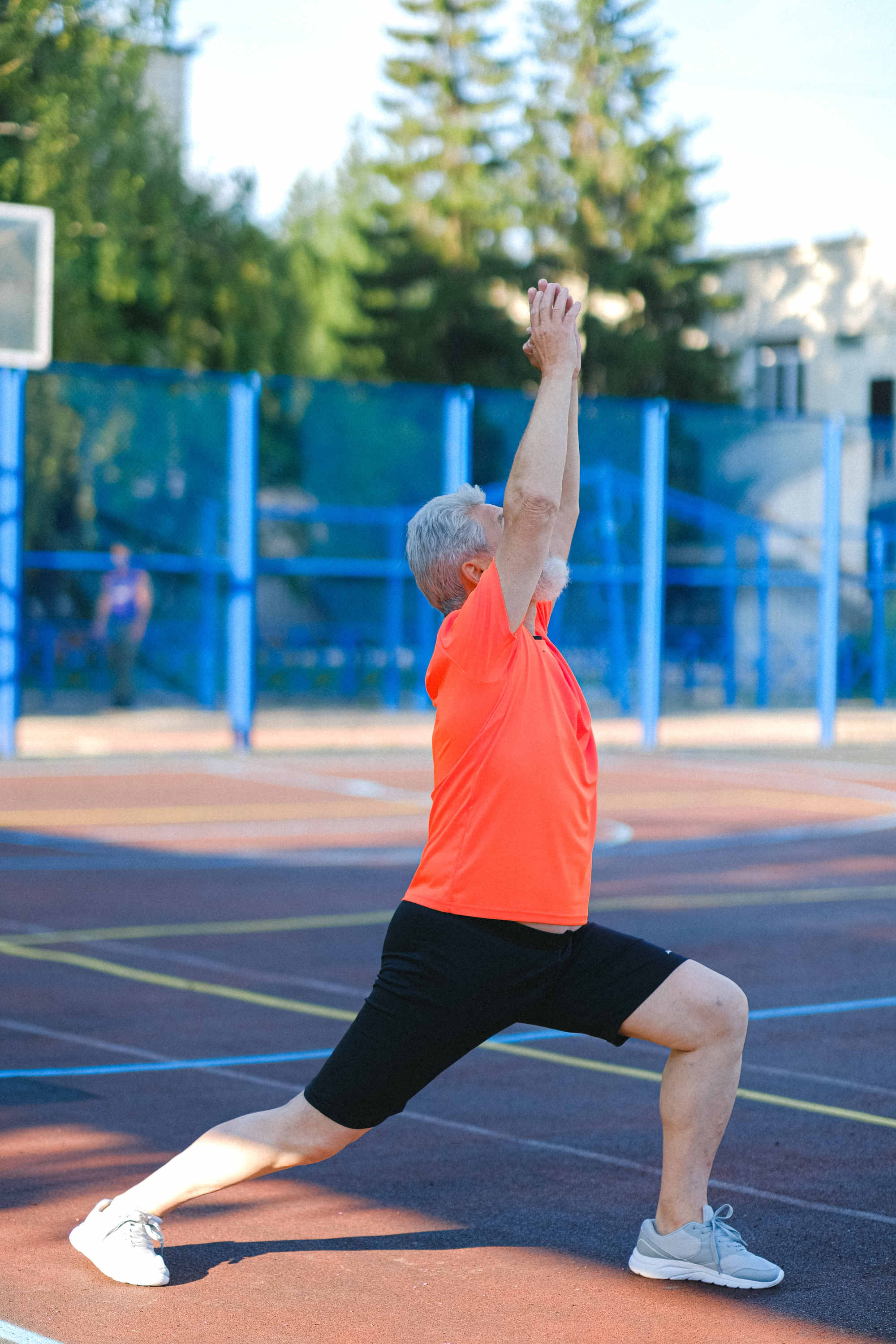 Older man in black shorts and orange shirt stretching in a park