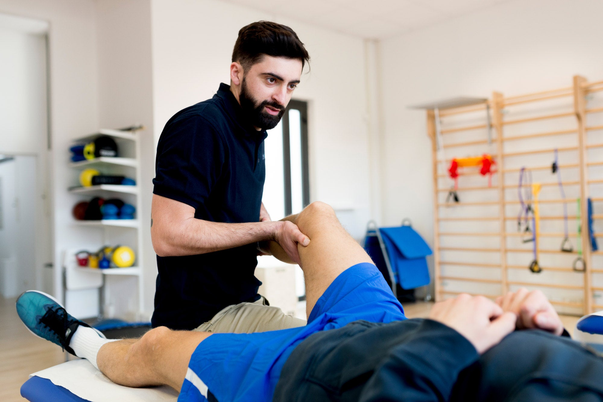 Physical trainer performing sports massage on athlete