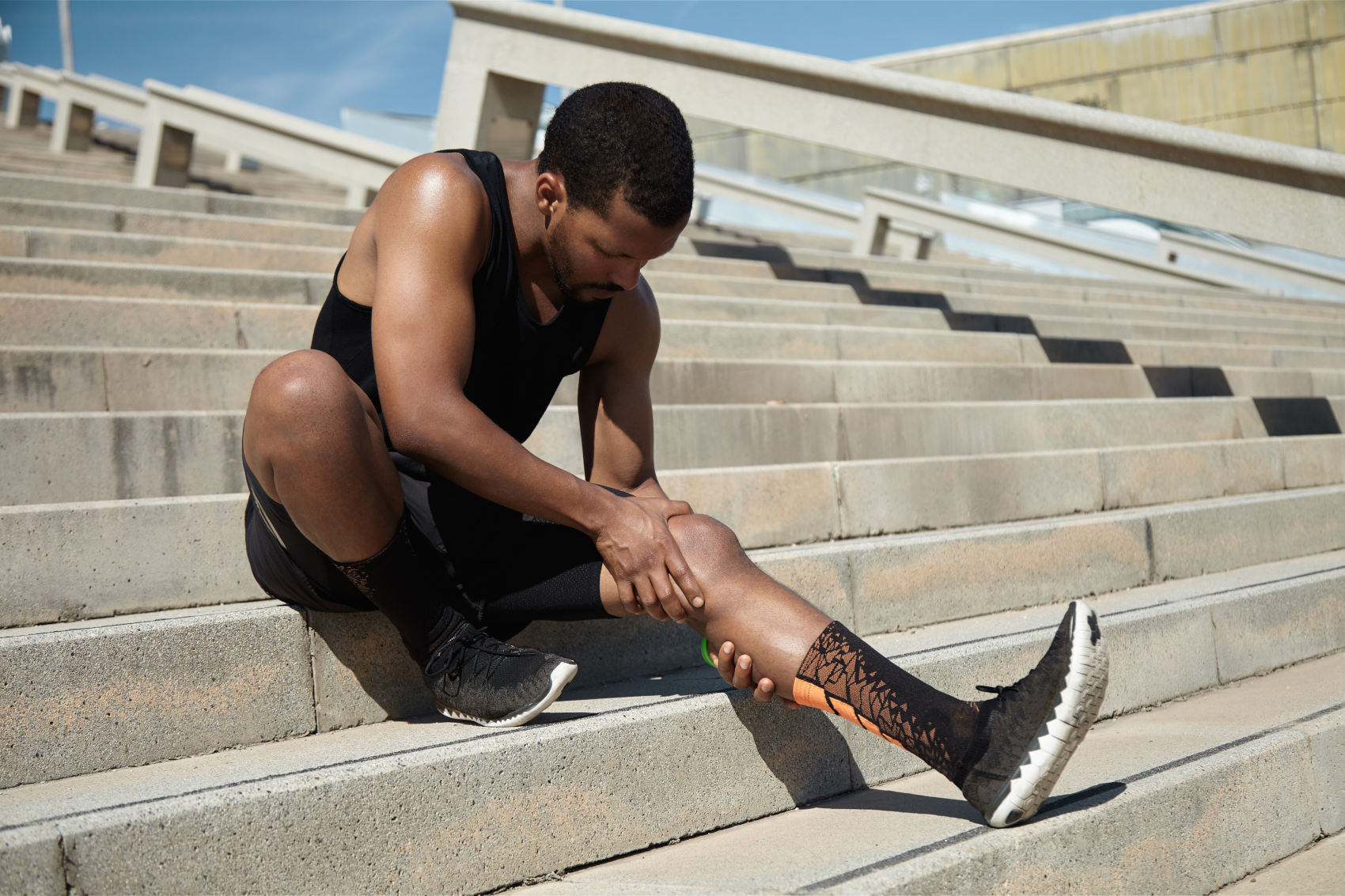 Handsome black runner with muscular athletic body holding his leg with both hands, feeling pain in knee or calf, massaging it, suffering from strain or spasm while sitting on steps of concrete stair