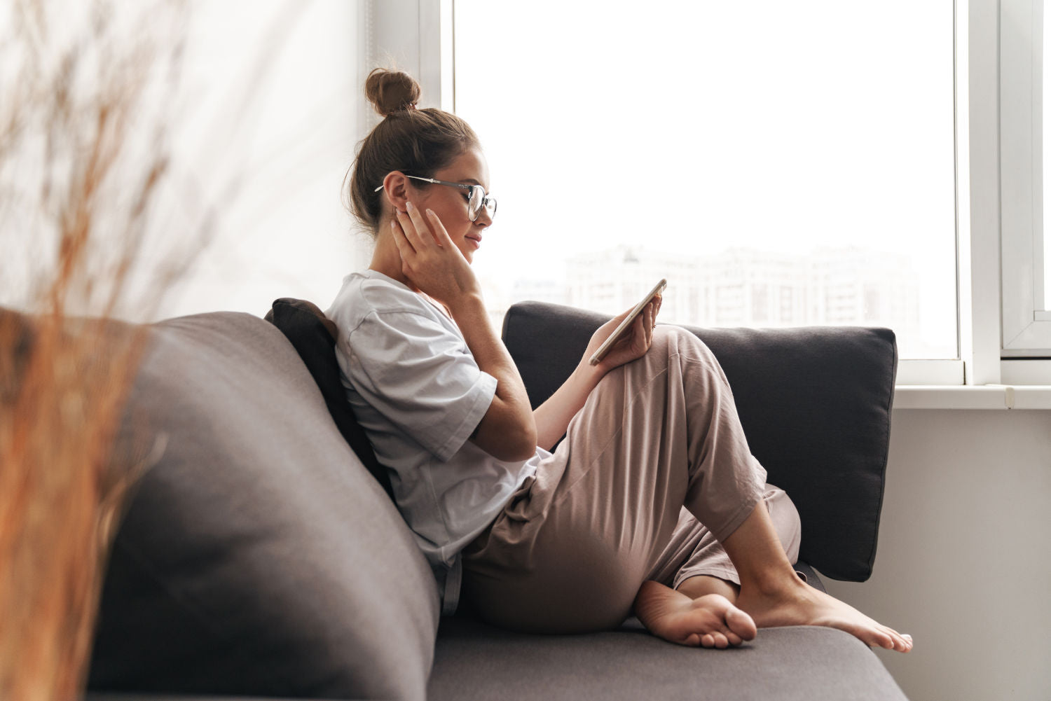 concentrated nice woman in eyeglasses using cellphone while sitting on sofa at living room
