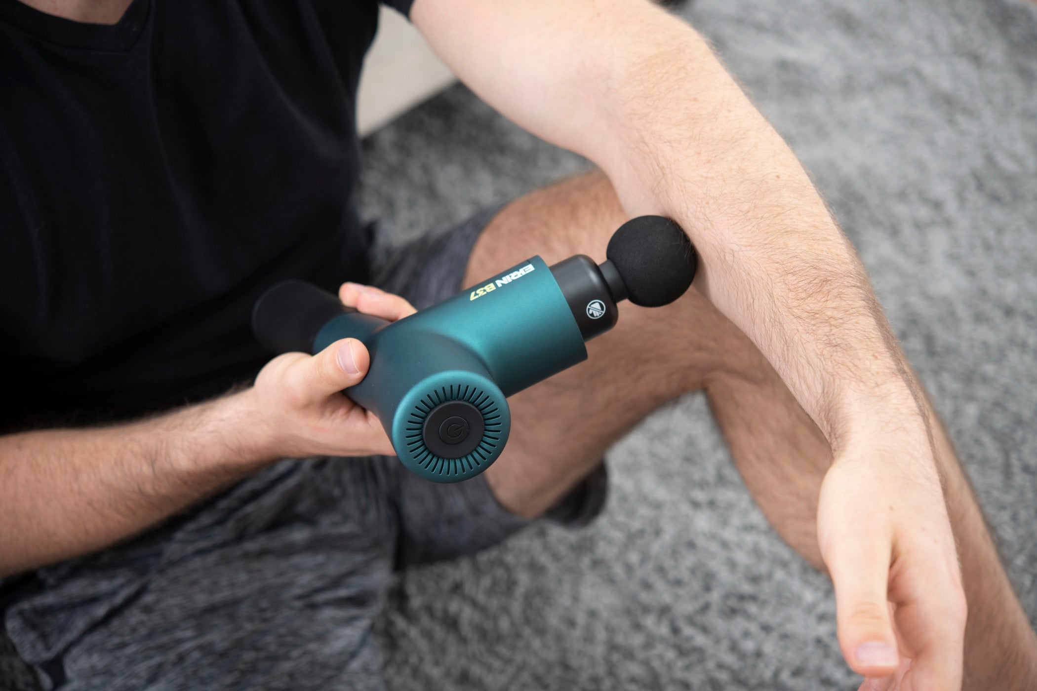 Man massaging forearm with Ekrin B37 while sitting on the floor