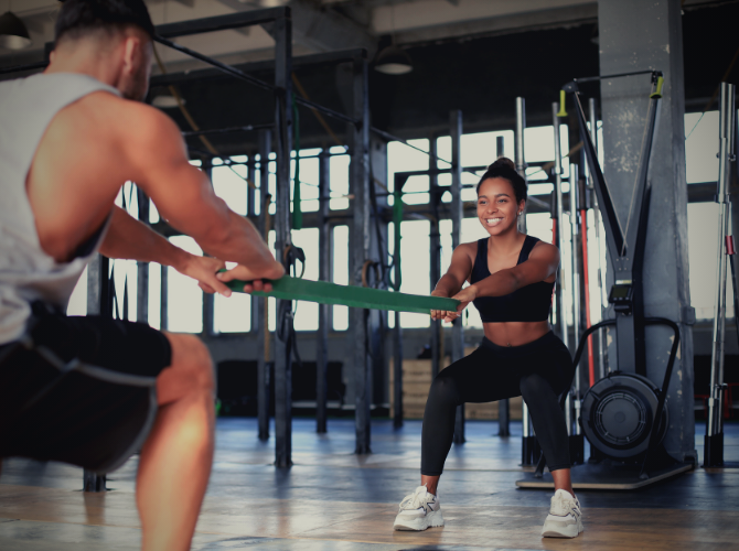 Man and woman at the gym exercising together with a smile