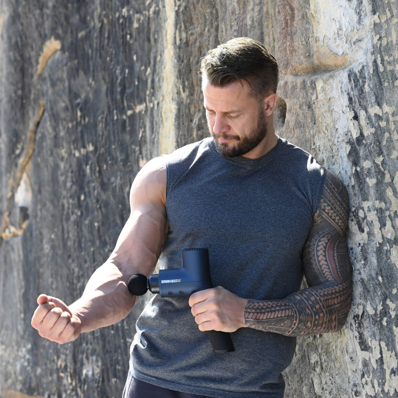 Bobby Holland Hanton outside in the sun leaning against a rock and massaging his forearm with the Ekrin B37S
