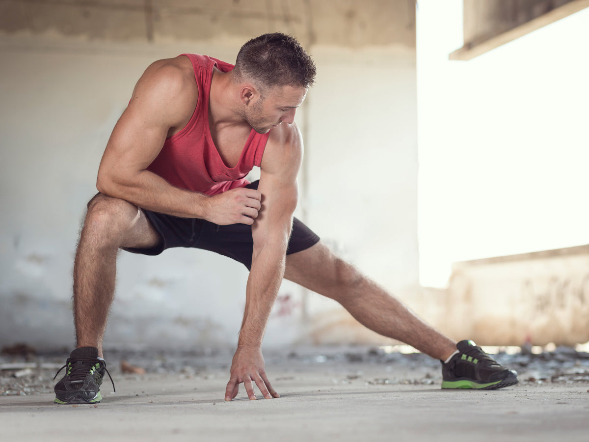 Athletic young man stretching outside