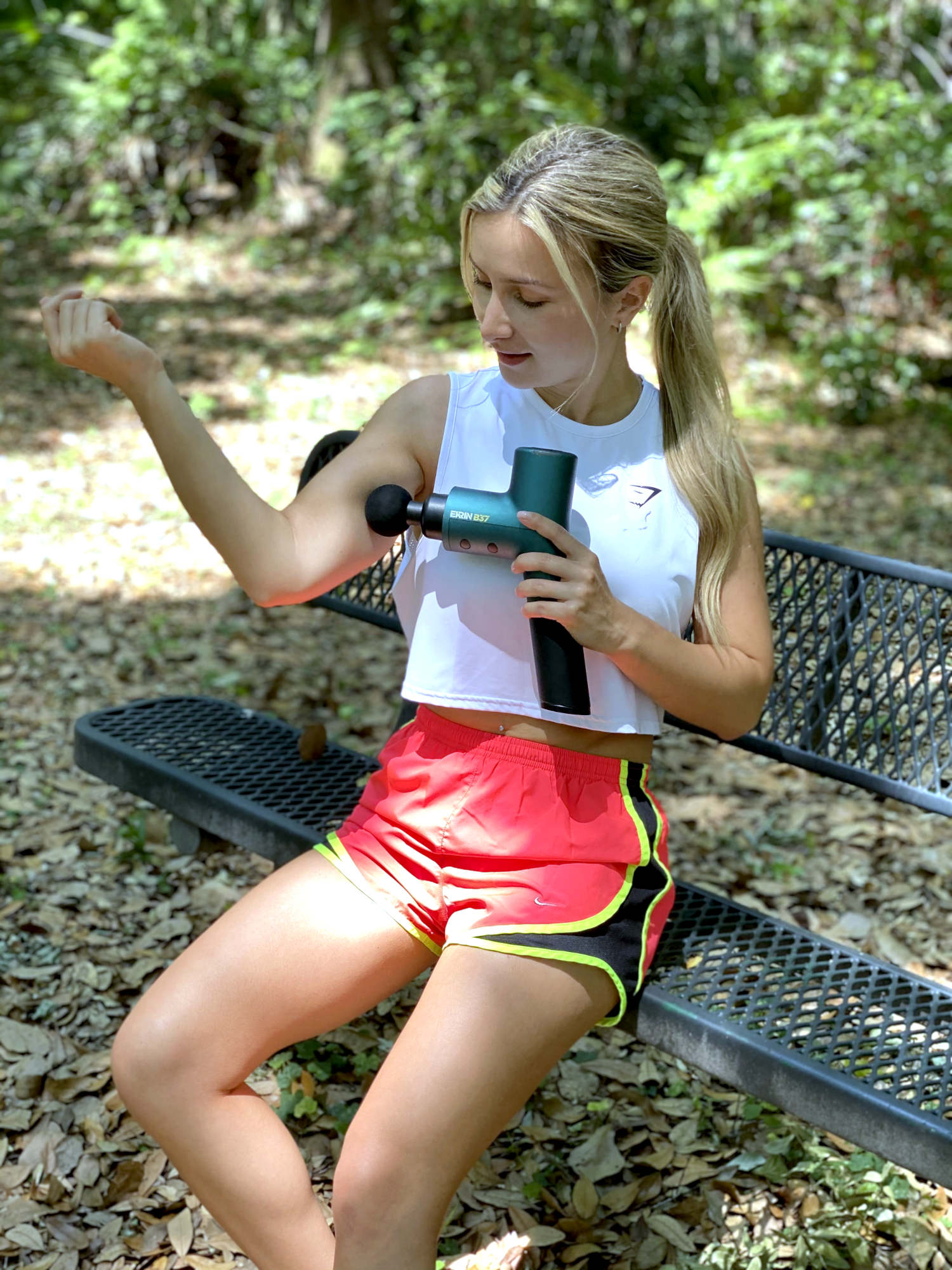 Woman in shorts massages her arm with a massage gun outside on a bench in a park