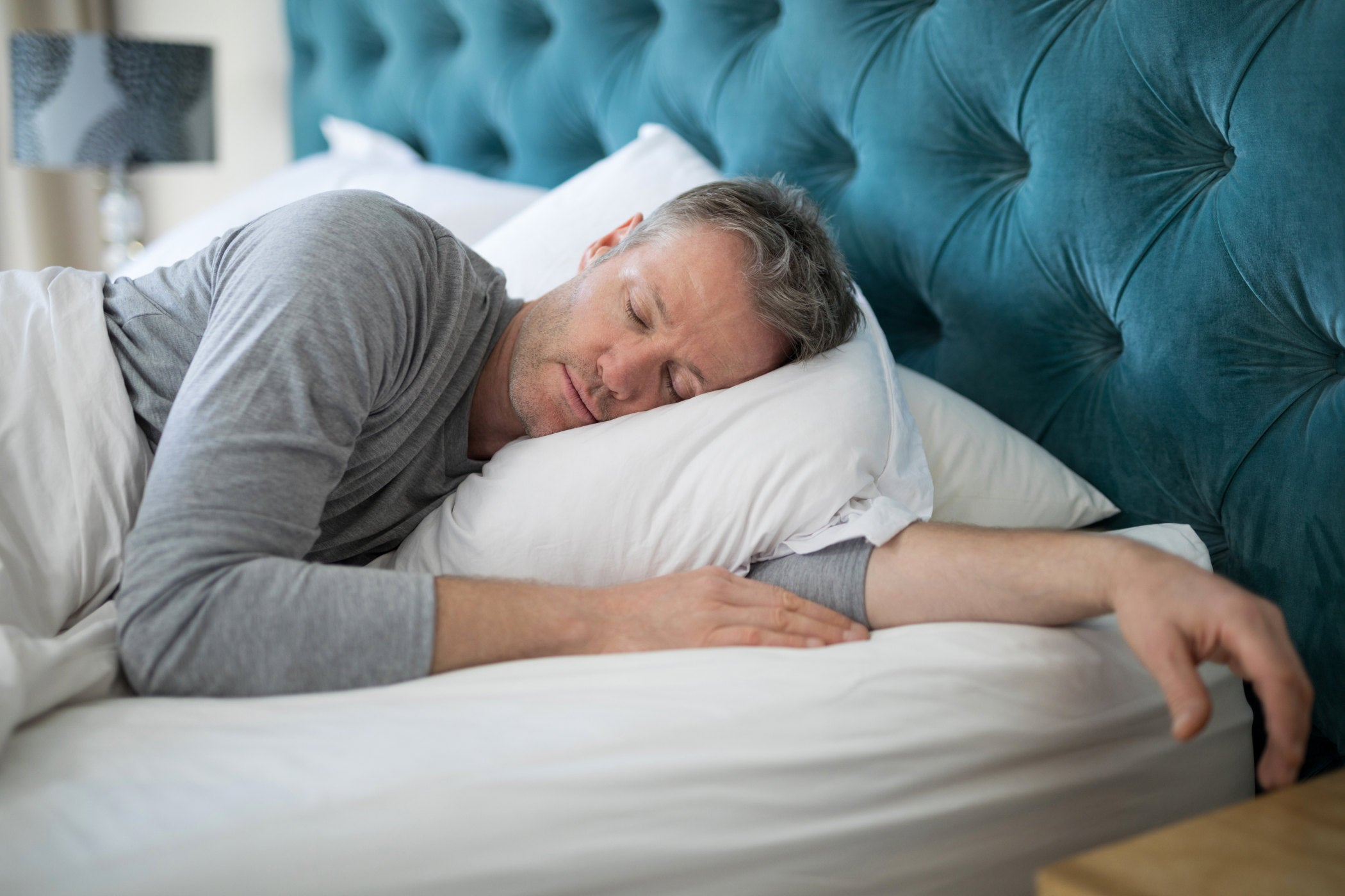 Man sleeping peacefully on a king sized bed with a blue tufted headboard