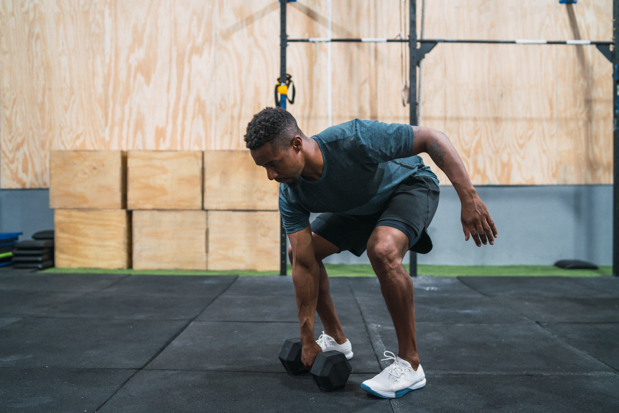 Portrait of young crossfit athlete doing exercise with dumbbell at the gym. Crossfit, sport and healthy lifestyle concept.