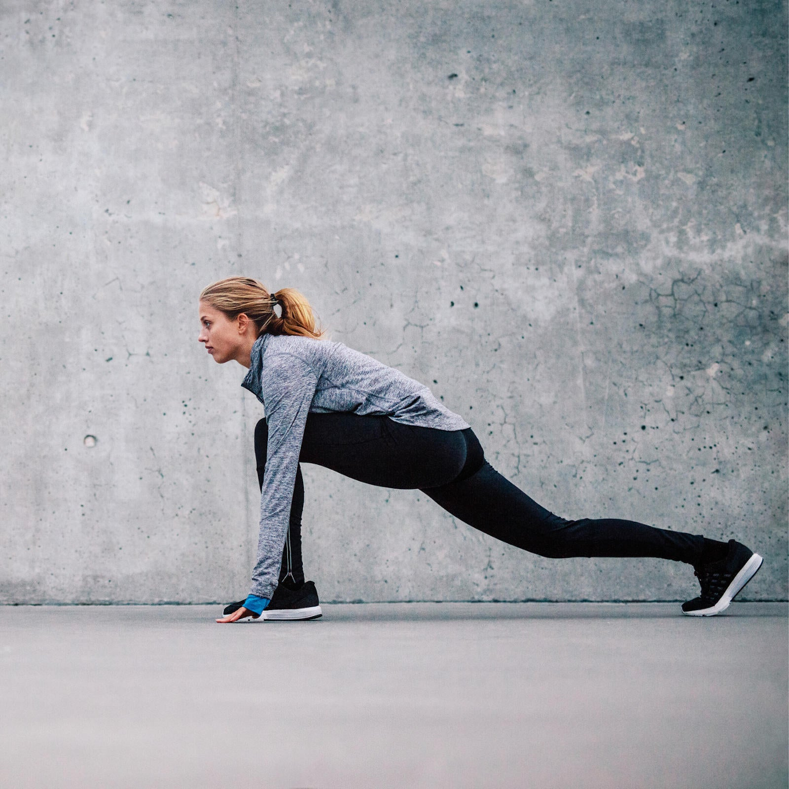 Athletic young woman stretching before going on a run
