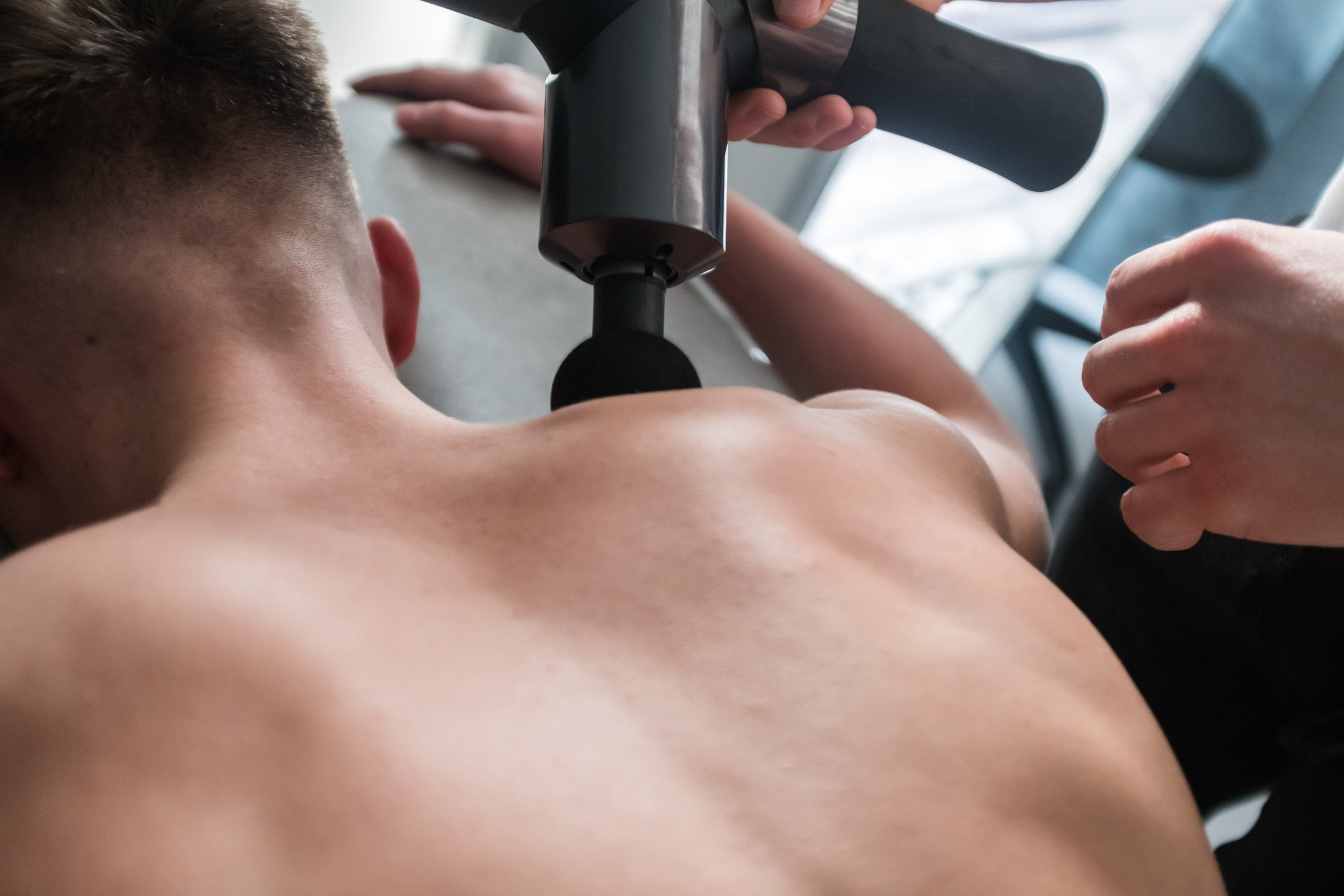 Massage therapy using a massage gun for sore back muscles