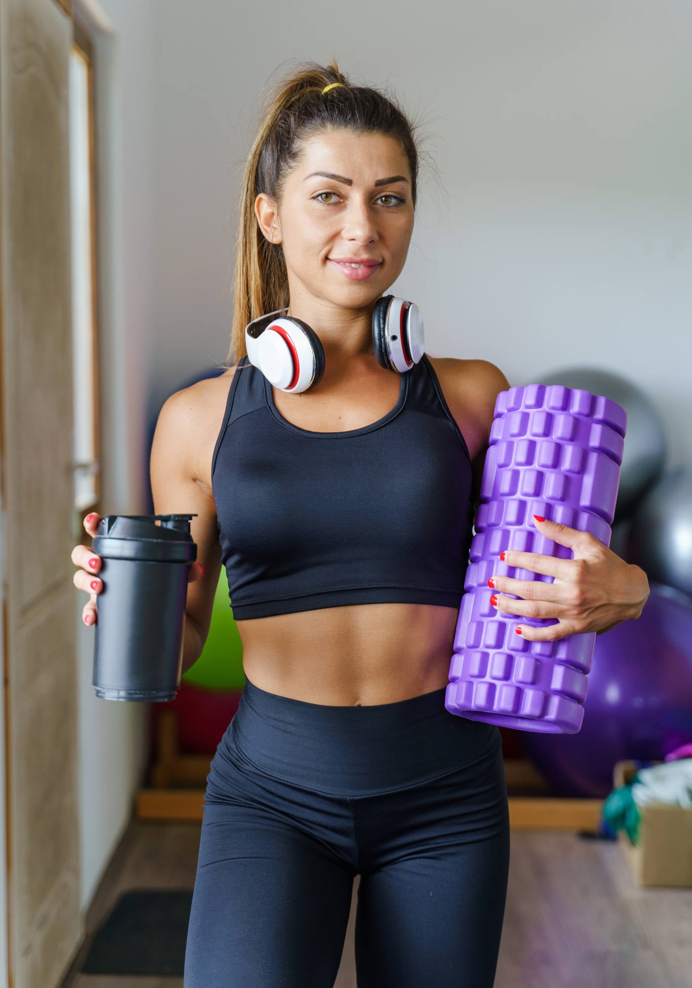 Front view on caucasian female instructor holding foam massage roller - Young muscular fitness woman going to fascia training - Sporty girl in leggins standing by the window Hold supplement shaker