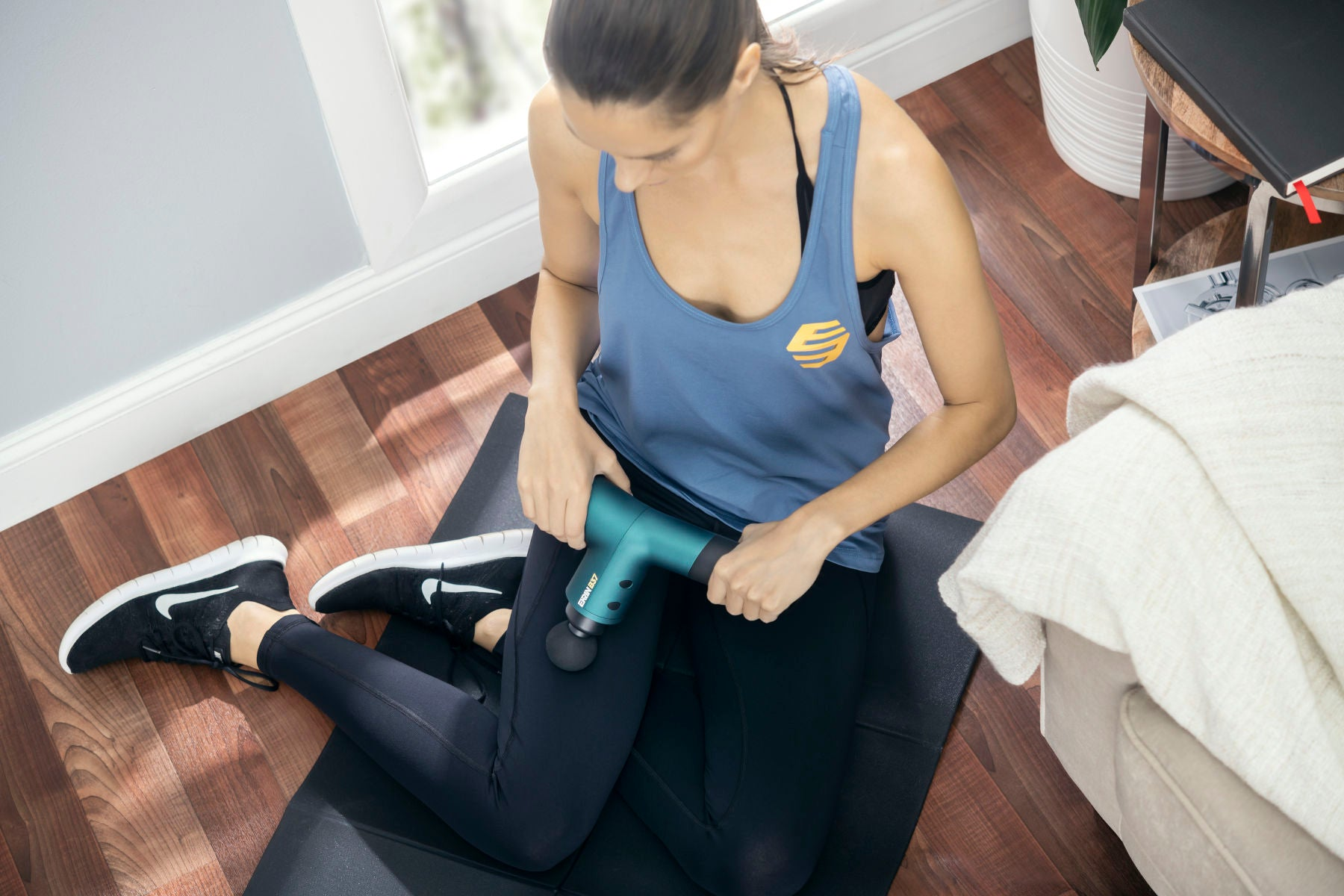 Athletic woman on the floor massaging her quad muscle with a green ekrin b37 massage gun