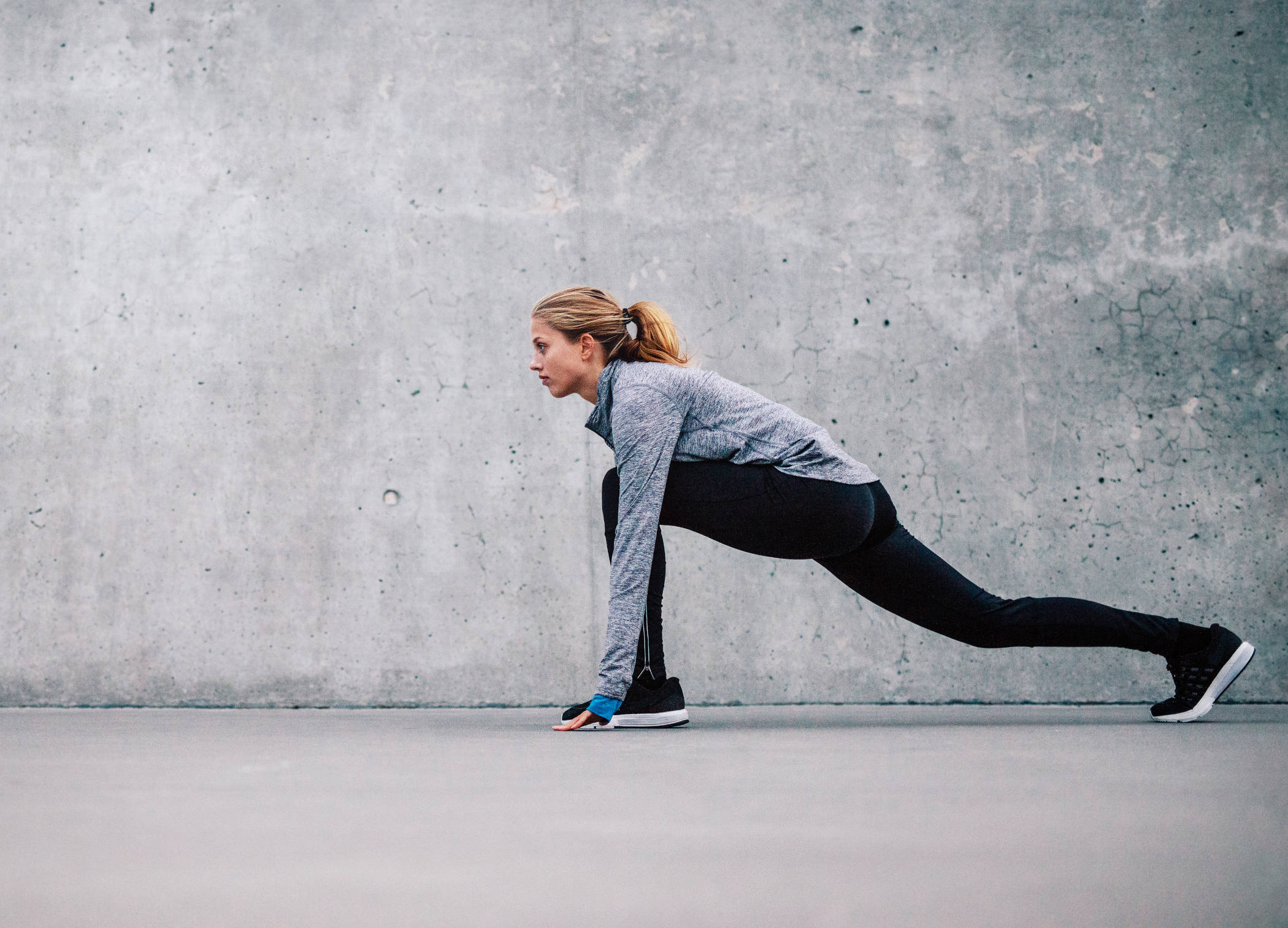 Young attractive cool sporty woman doing crisscross fitness exercise, bicycle crunches, working out on the floor, wearing black sportswear bra and black pants, full length at home or sports center