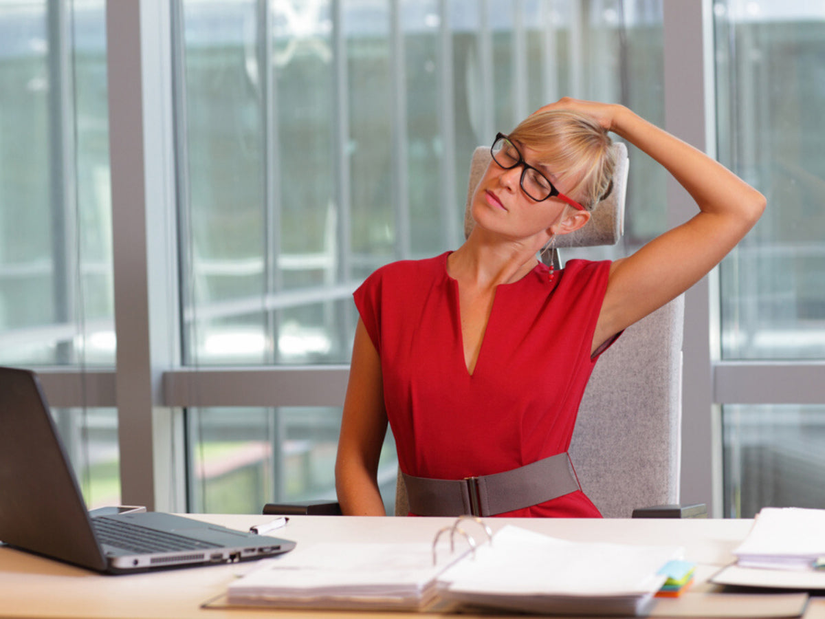 Young woman stretching her neck at her desk in an office
