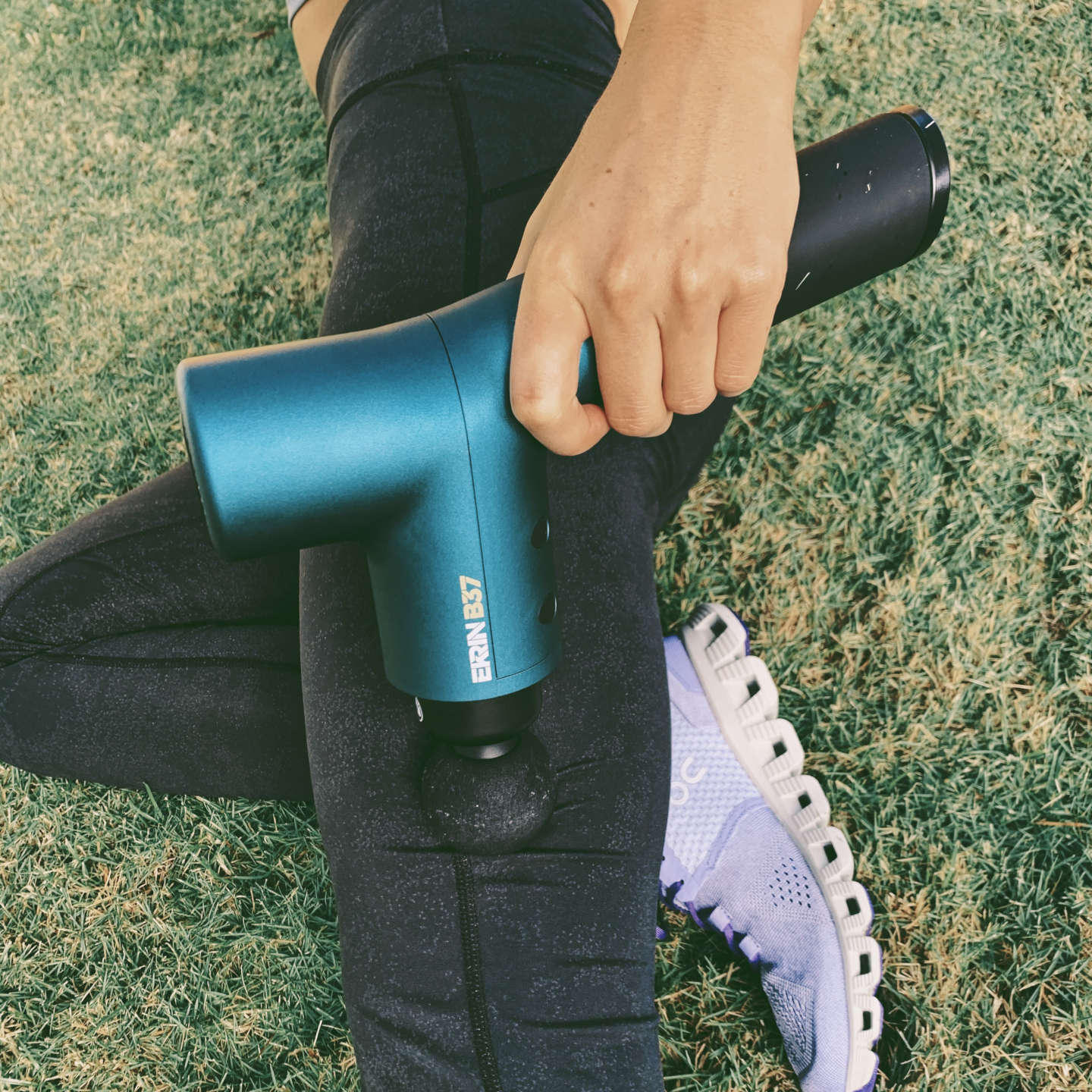 Athletic woman massaging her muscles with a massage gun outside on grass