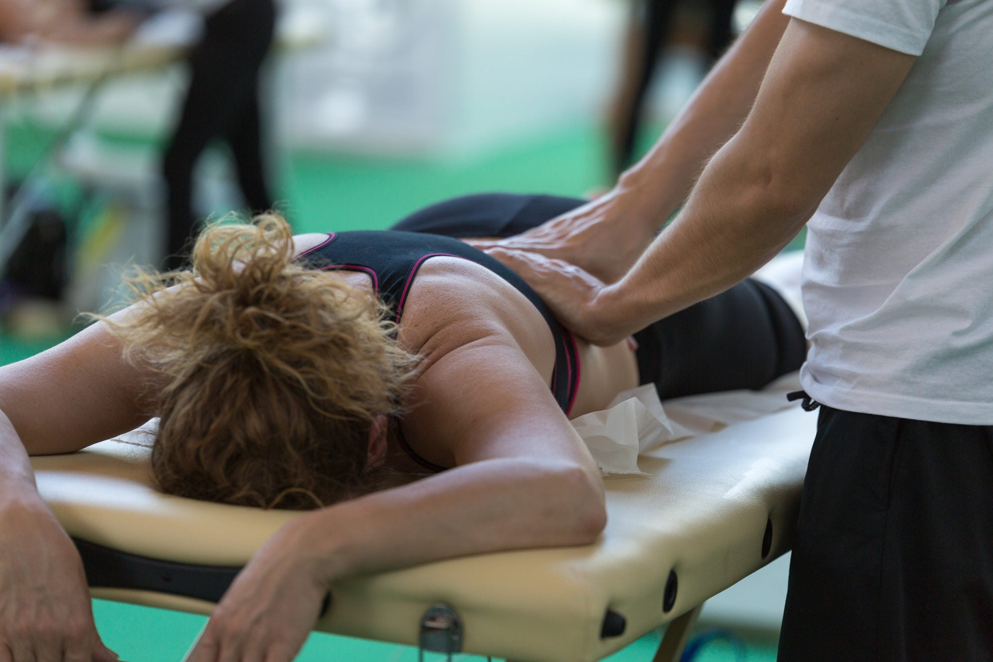Athletic woman getting back massage after working out