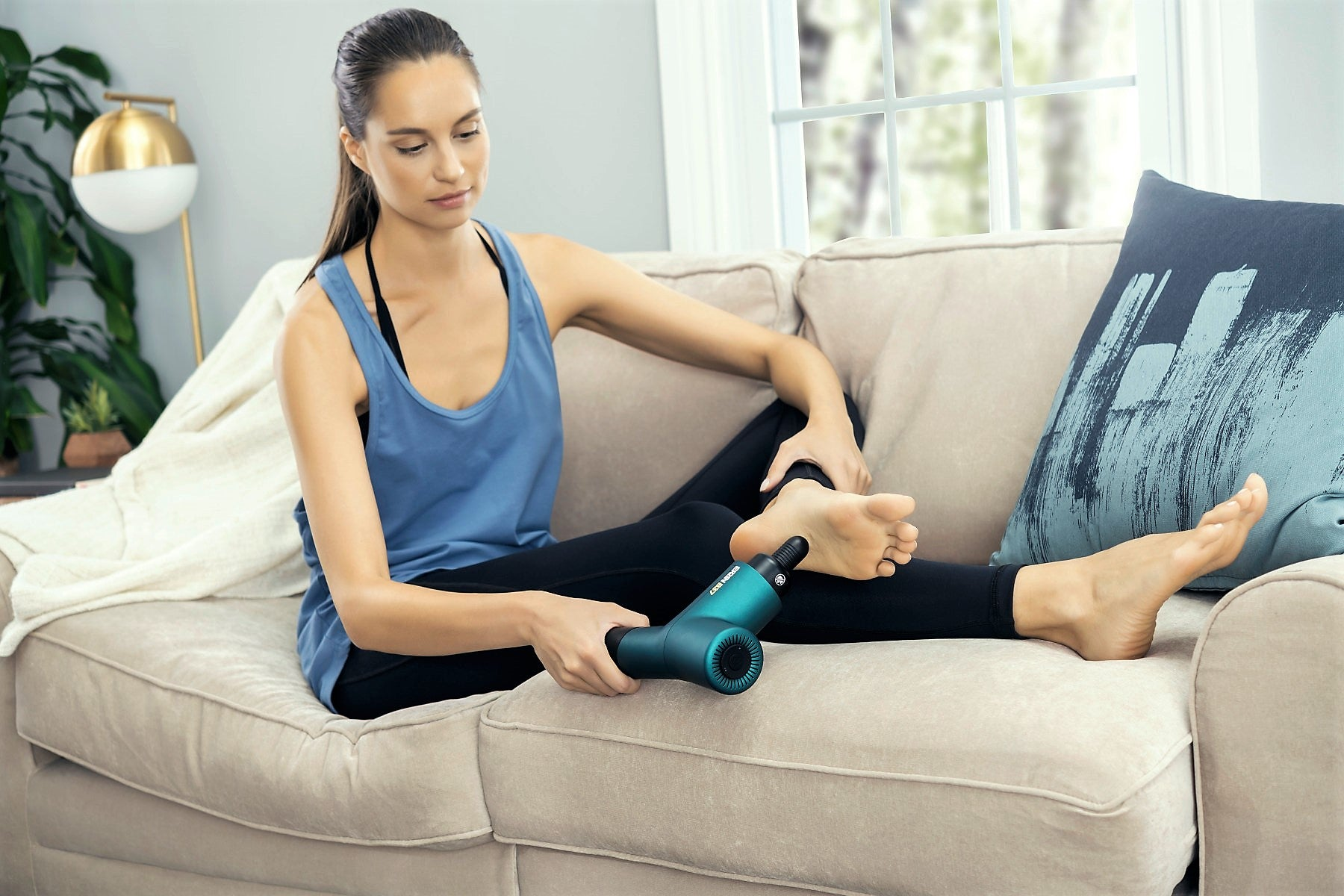 Young woman massaging her foot in her living room with a massage gun