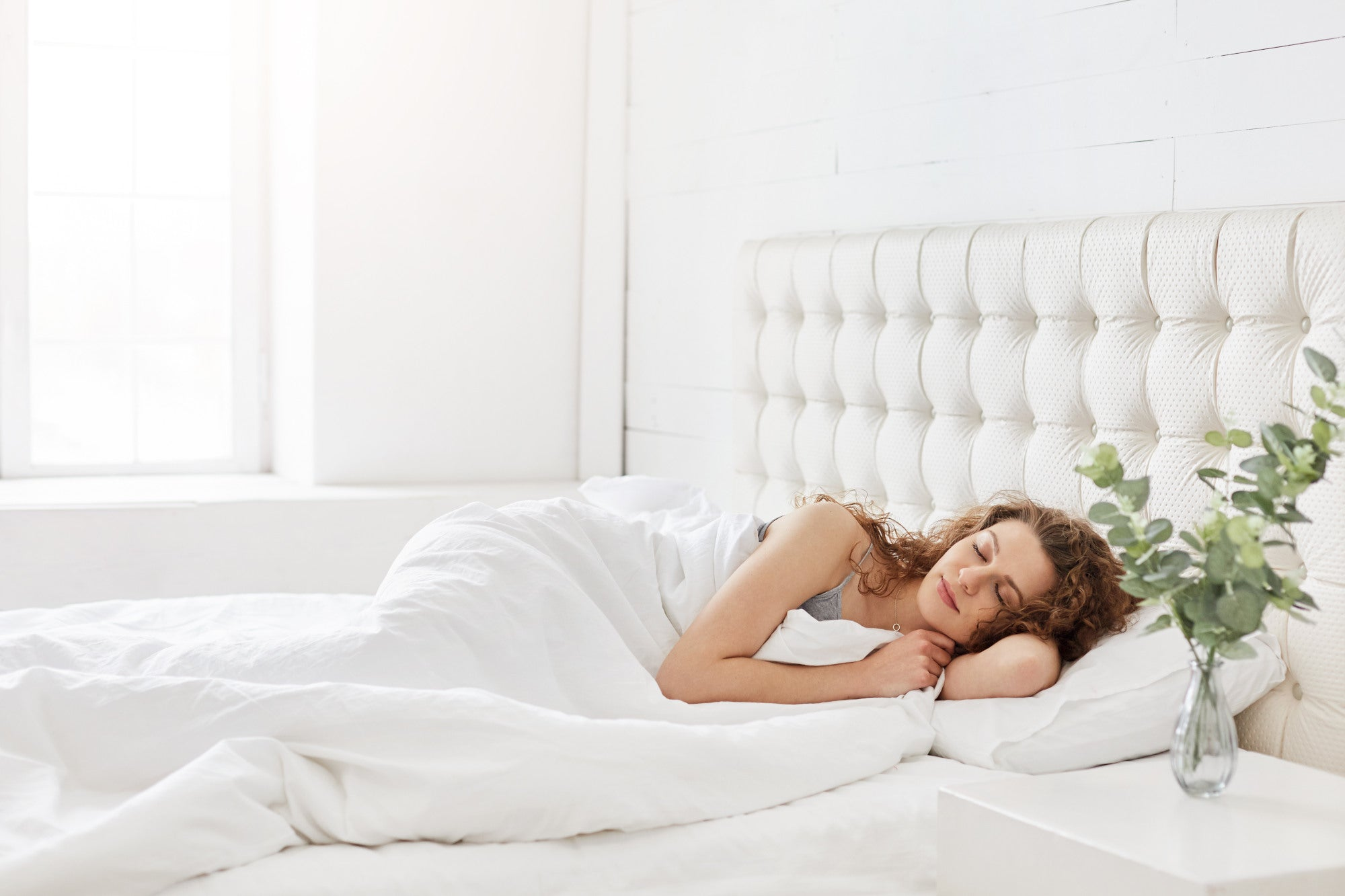 Young woman sleeping on white bed with white sheets
