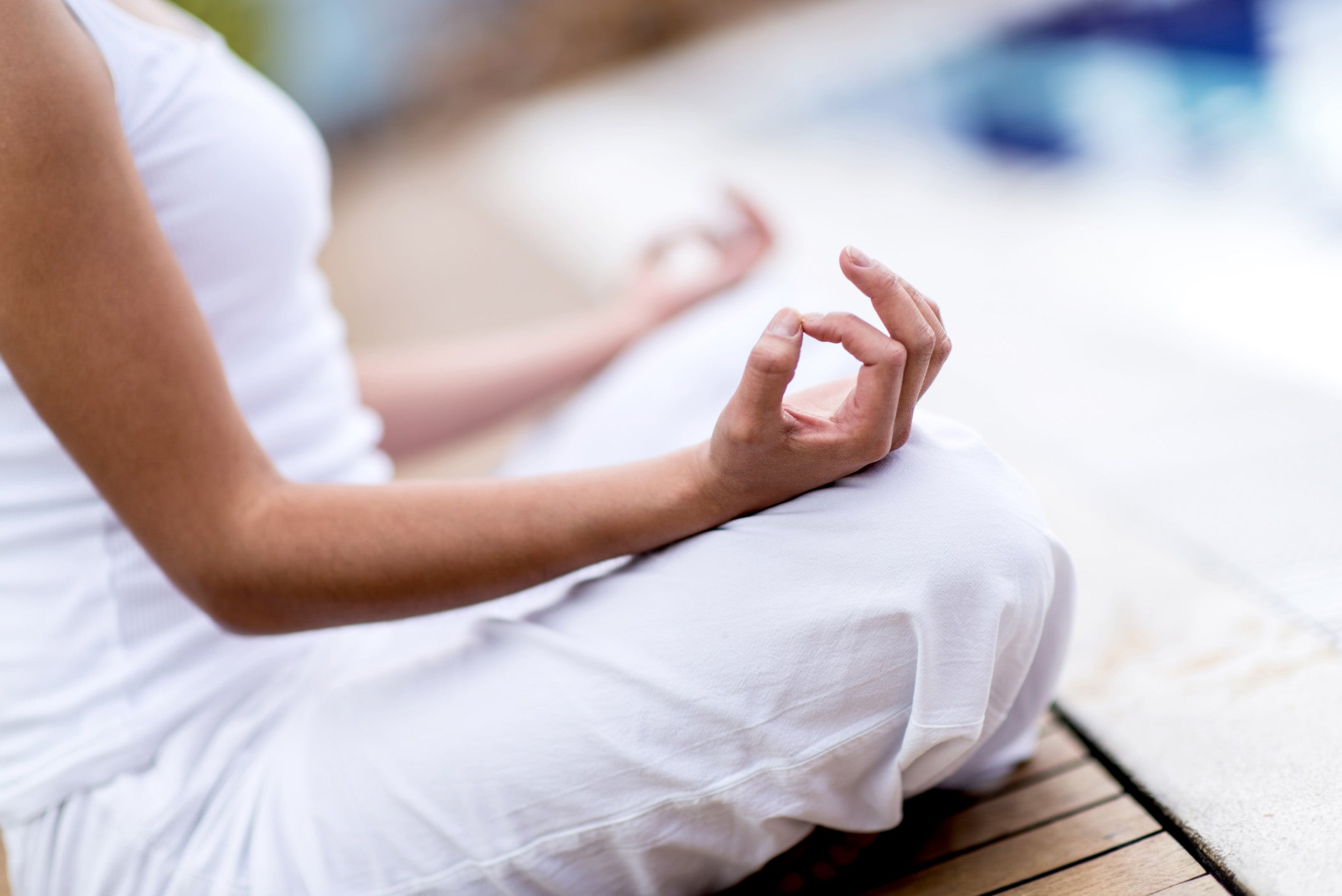 Healthy woman practicing yoga in white clothing