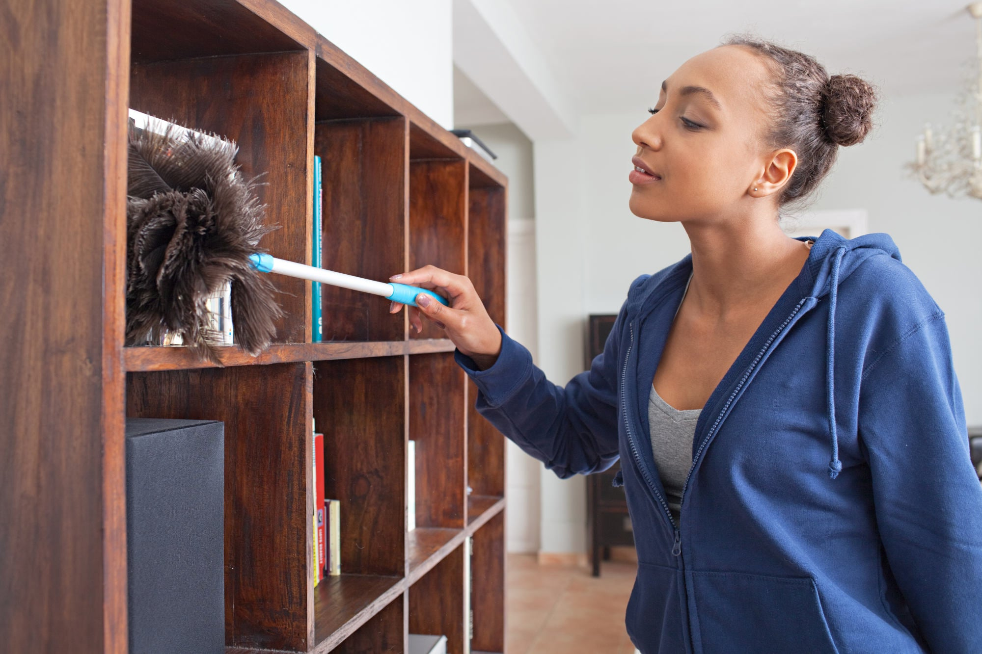 Portrait of beautiful african american teenager using a feather duster to clean wood book shelves in home living room, smiling indoors. Young female spring cleaning house interior, skills and chores.
