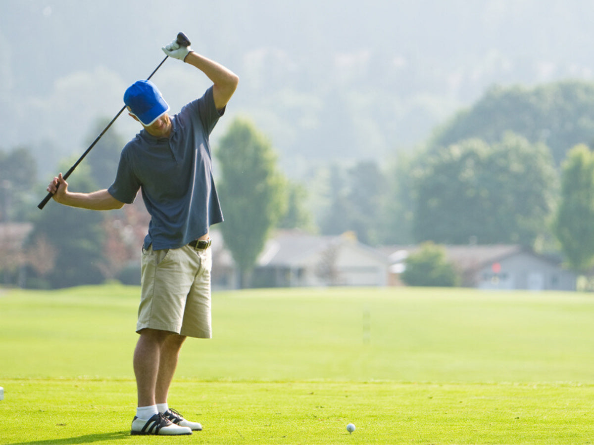 Young man stretching before golfing on a sunny day