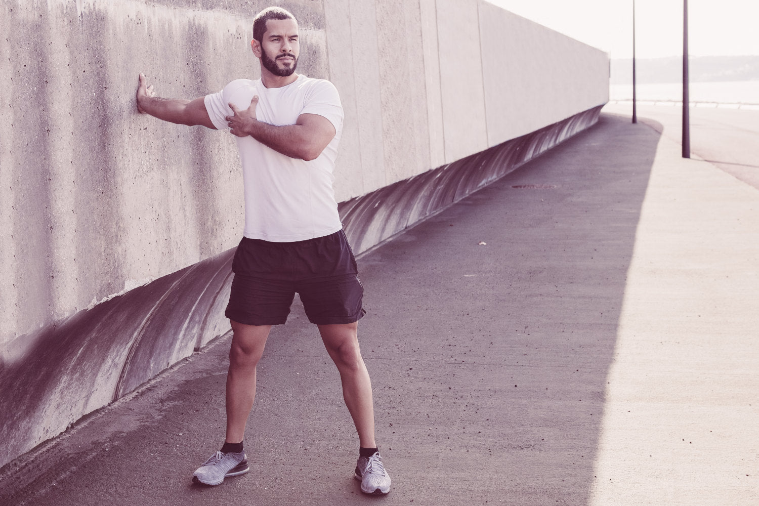 Man using a concrete wall to stretch shoulder