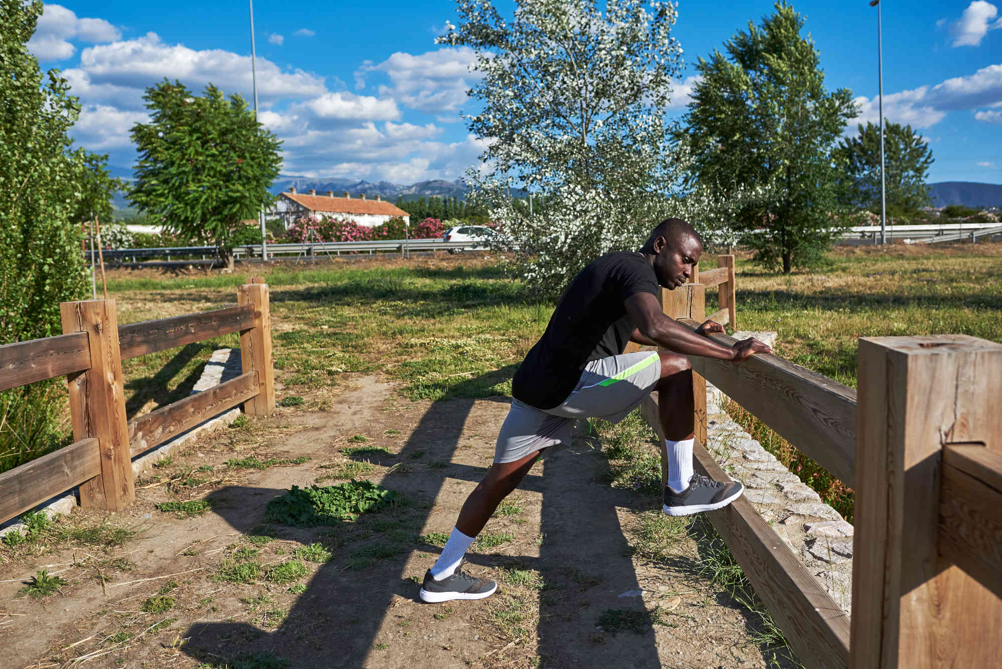 Sportsman stretching a sunny summer day. He is in an urban park.