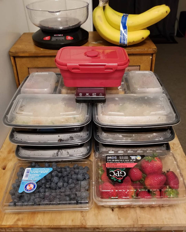 The Truweigh Crimson food scale sits on top of a pile of six meal prep containers that are filled with food. A large container of blueberries and a large container of strawberries are in front. Behind, a bunch of bananas and the Truweigh Vortex kitchen sc
