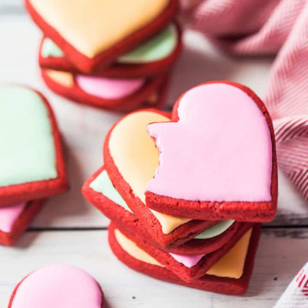 Red Velvet heart-shaped cookies for Valentine's Day. Stacks of cookies with pink, yellow or green frosting are arranged, and the pink cookie on top of the front stack has a bite taken out of it. Photo credit to the Baking a Moment blog
