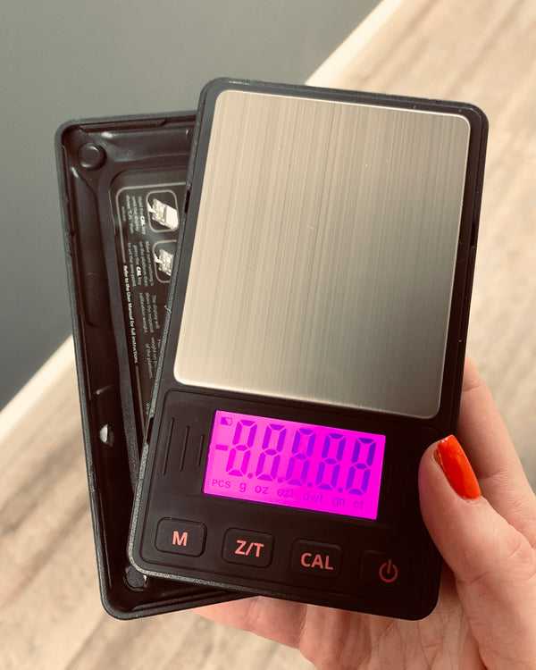 A female hand holds the Pink Truweigh Riot digital pockets scale with the cover showing behind it, the scale is on with the pink backlight visible.