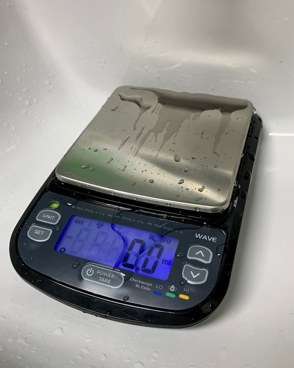 The Truweigh Wave Digital Washdown Scale sits in a white sink after being cleaned. There is water on the platform and screen, and the screen is turned on, reading 0.0g
