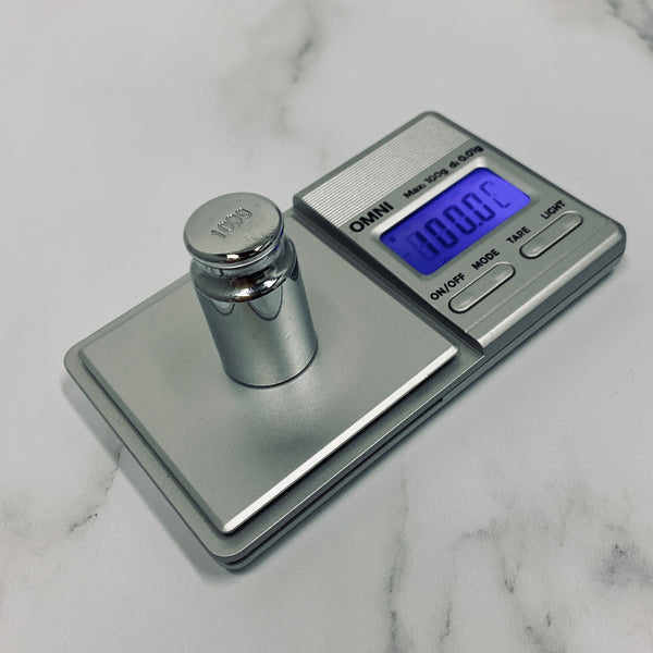 The Truweigh Omni Digital scale sits on a white marble background and is being calibrated with a 100g chrome calibration weight. The blue back-lit screen reads 100.00g.