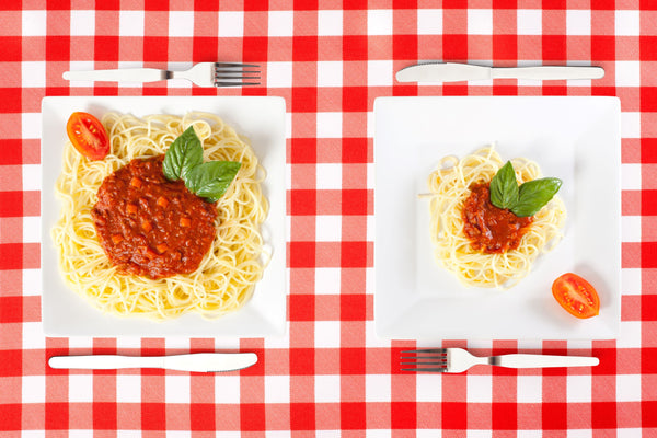 Two square white plates are next to each other with a knife and fork on either side, both on a table with a red and white checkered tablecloth. The left plate has a large portion of spaghetti and meat sauce and the right plate has a much smaller portion.