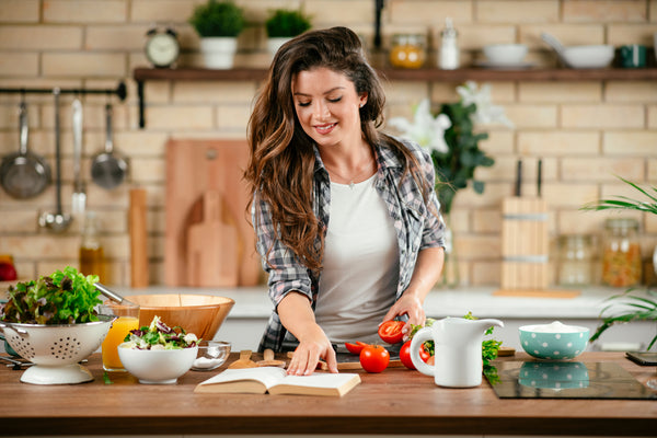 A pretty young brunette woman reads a recipe in her kitchen as she prepares to make a meal. She has all sorts of ingredients on the counter in front of her, and pots, pans, cutting boards and knives can be seen on the counter behind her.