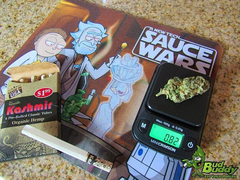 The Truweigh Mini Crimson digital scale is weighing a large cannabis nug that weighs 0.82 grams. The scale is on a Rick and Morty Sauce Wars dab mat, with a box of Kashmir pre-rolled cones laying next to it.