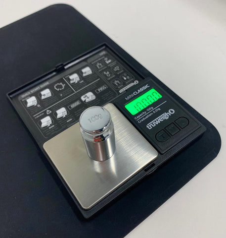 The Truweigh Mini Classic digital scale sits on a black mat on a white countertop with a 100g calibration weight on the platform. The green screen reads 100.00g