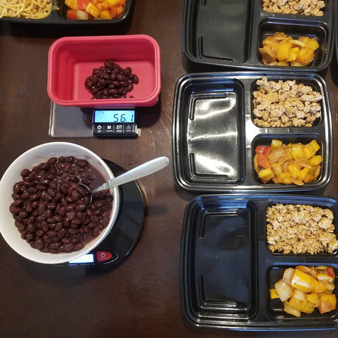 A meal prep station is shown from above. A bowl of beans is being measured into the Truweigh Crimson weighing bowl on the scale, and four meal prep containers are set up and already filled with protein and vegetables.