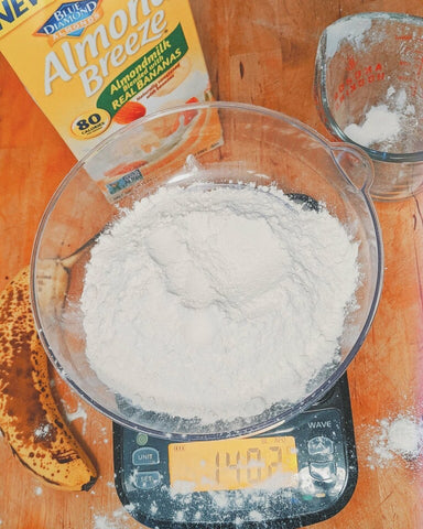 Truweigh Wave scale has a large bowl of flour on it, with flour spilled outside of the bowl. The scale is on an orange background, and a measuring bup, banana and almond milk are also in the frame.